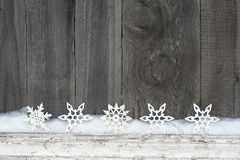 Rustic winter background with glitter snowflakes and snow on wooden texture. Christmas and New Year greeting card background stock photos