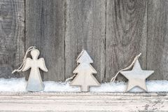 Rustic winter background with wooden figures star, Christmas tree and angel with snow on wooden texture. Christmas and New Year. Greeting card background stock image