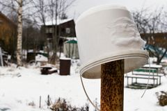 Rustic winter landscape with an old white plastic bucket on an iron rusty pillar. royalty free stock photo