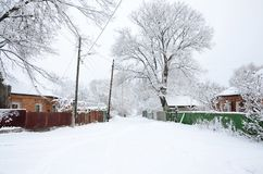 A rustic winter landscape with some old houses and a broad highway covered with a thick layer of snow.  Stock Photos