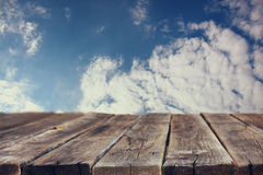 Rustic wood board in front of sky with clouds. Stock Images