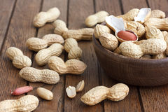 Rustic wood bowl of peanuts in shells. Stock Images