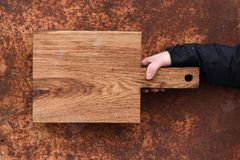 Rustic wood cutting board held in hand on corroded metal texture Royalty Free Stock Photos