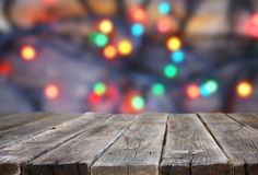 Rustic wood table in front of glitter colorfull bright bokeh lights. Royalty Free Stock Photo