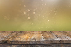 Rustic wood table in front of glitter green and gold bright bokeh lights