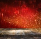 Rustic wood table in front of glitter red and gold bokeh lights Stock Photography