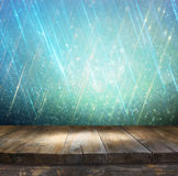 Rustic wood table in front of glitter silver, blue, and gold bokeh lights Stock Photo