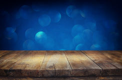 Rustic wood table in front of glitter silver, blue, and gold bokeh lights.  royalty free stock photos