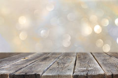 Rustic wood table in front of glitter silver and gold bright bokeh lights. Royalty Free Stock Photo