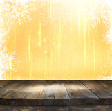 Rustic wood table in front of glitter silver and gold bright bokeh lights with snowflacke overlay Stock Photo