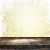 Rustic wood table in front of glitter silver and gold bright bokeh lights with snowflacke overlay Stock Images