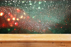 Rustic wood table in front of glitter silver, green, blue and gold bright bokeh lights Stock Images