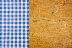 Rustic wooden background with a blue checkered tablecloth Stock Image