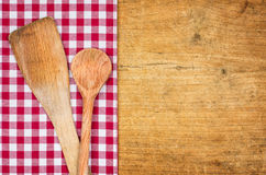 Rustic wooden background with a checkered tablecloth and wooden spoons royalty free stock images