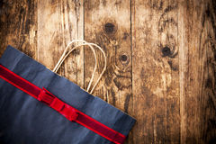 Rustic wooden background paper bag. Royalty Free Stock Photo