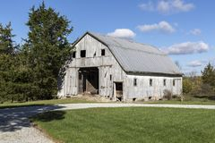 A rustic wooden barn in rural area. A wooden barn in a rural scene with a beautiful blue sky and billowing white clouds Royalty Free Stock Images