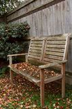 Rustic wooden bench covered in autumn leaves Royalty Free Stock Image