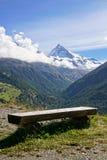 Rustic wooden bench overlooking Swiss Alps. Stock Images