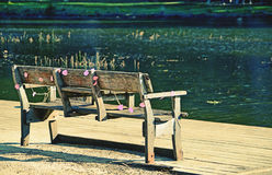 Rustic wooden bench on riverbank Stock Photography