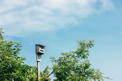 Rustic wooden birdhouse hight in the sky, summer home, space for. Text Stock Image