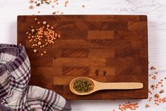 Rustic wooden board, checkered napkin and lentils seeds with cop. Y space for your menu or recipe. Menu card for restaurants stock image