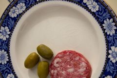 Rustic wooden board with an old plate and some slices of salami and olives royalty free stock image