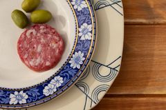 Rustic wooden board with an old plate and some slices of salami and olives. Free space to write royalty free stock photos