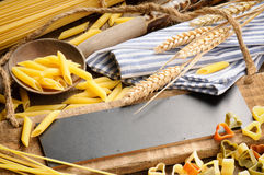 Rustic wooden board with pasta assortment. And tablecloth Stock Images