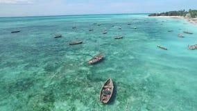 Rustic wooden boats for fishing, Zanzibar, Tanzania, aerial. Rustic wooden boats for fishing sitting in calm waters of Zanzibar, Tanzania, aerial stock footage