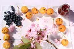 Rustic wooden breakfast background with bluberries, fresh scones and blooming cherry flowers Royalty Free Stock Photos
