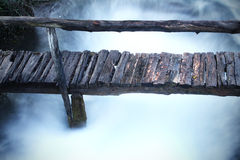 Rustic Wooden Bridge On The River Stock Photo