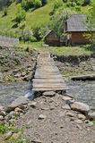 Rustic wooden bridge over a stream Stock Image