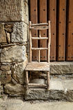 Rustic wooden chair. Photo shows small, hande made, rustic, wooden chair with Welcome inscription. The chair stays near the stone wall and on the front of wooden Royalty Free Stock Photography