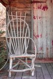 Rustic Wooden Chair on Porch of Mini Wooden House. A small, mini house, made of wood with rustic, wooden chair on the front porch.  Located in the historical Royalty Free Stock Images