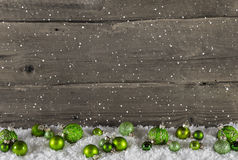 Rustic wooden country background with green christmas balls. Rustic wooden country background with green christmas balls and snow Royalty Free Stock Photography
