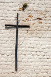 Rustic Wooden Cross. A rustic wooden cross on a white brick wall Royalty Free Stock Photography