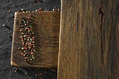 Rustic wooden desk and black table background with colour pepper royalty free stock photos