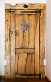 Rustic wooden door with hammered iron reinforcement, heart shaped ornament, private Royalty Free Stock Images