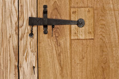 Rustic wooden door with hammered old fashioned iron lock Stock Photos
