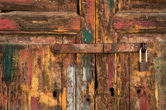 Rustic Wooden Door with Padlock and Worn Paint Royalty Free Stock Image