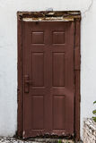 Rustic wooden door on white wall Royalty Free Stock Images
