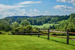 Rustic Wooden Fence - Rolling Hills. A rustic wooden fence on a hill overlooking the rolling hills of Wisconsin countryside stock image