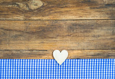 Rustic wooden heart and blue checkered fabric on brown plank. Royalty Free Stock Photo