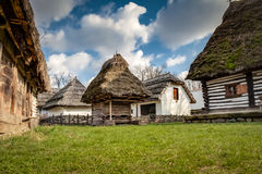 Rustic wooden houses with thatched roofs Stock Photos