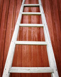 Rustic wooden ladder on red background Royalty Free Stock Images