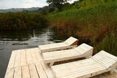 Rustic Wooden Lake Lounge Chairs. Three white and wooden lake lounge chairs Stock Photography