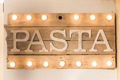 Rustic wooden pasta board. Pasta sign made of wooden planks and light bulbs on top and bottom Stock Images