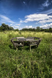 Rustic wooden picnic bench in meadow under blue sky Stock Photo