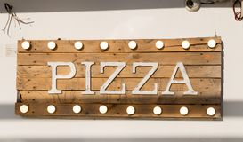 Rustic wooden pizza sign. Pizza sign made of wooden planks and light bulbs on top and bottom Stock Photos