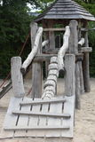Rustic wooden playground equipment. In the form of a challenging ramp leading up to a small hexagonal hut Stock Photos